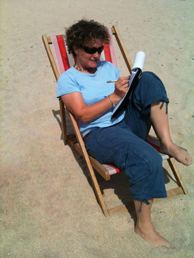 Liz Kessler writing on the beach